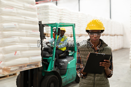 female worker writing on clipboard in