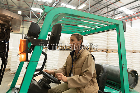 female worker driving forklift in warehouse