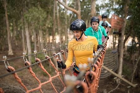 friends walking on rope bridge