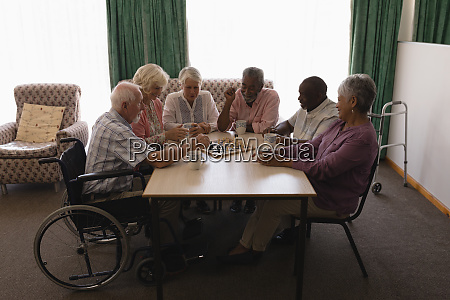group of senior people playing chess
