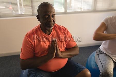 senior men performing yoga at home