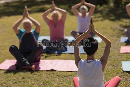 female trainer training senior people in