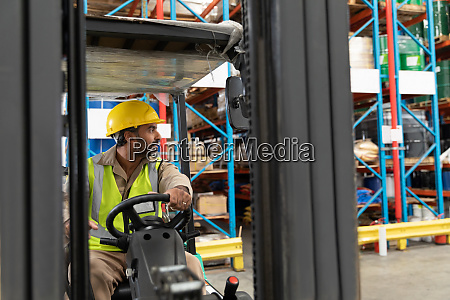 male staff driving forklift in warehouse