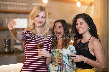portrait of female friends taking selfie