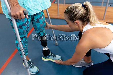 female physiotherapist assisting disabled senior woman