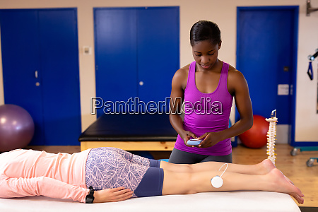 physiotherapist giving electro stimulation to active