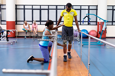 physiotherapist assisting disabled man walk with