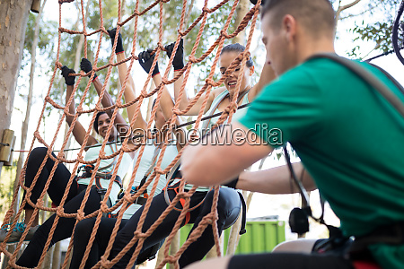 coach assisting trainee in net climbing