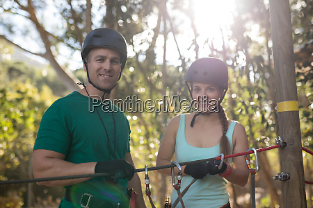 coach assisting trainee in zip line