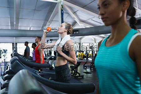woman drinking water while exercising on