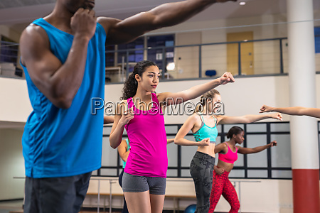 fit people exercising together in fitness
