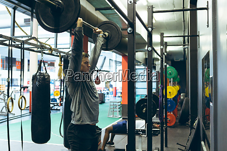 male athletic exercising with barbell in