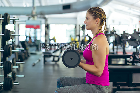 female athletic exercising with dumbbell in