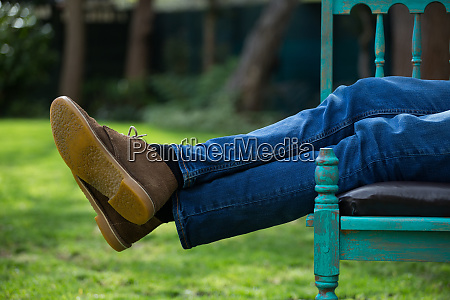 man lying on bench in garden
