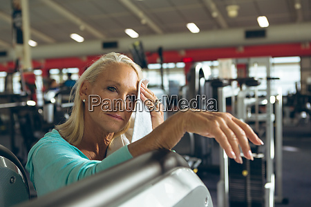 tired active senior woman wiping sweat