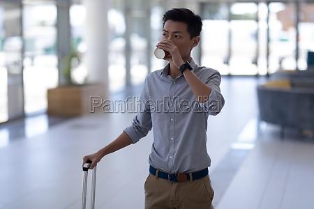 asian male executive having coffee while