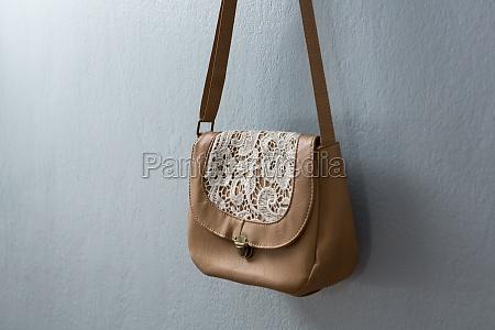 stylish handbag hanging against wall