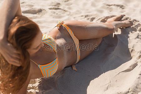 young caucasian woman in bikini lying