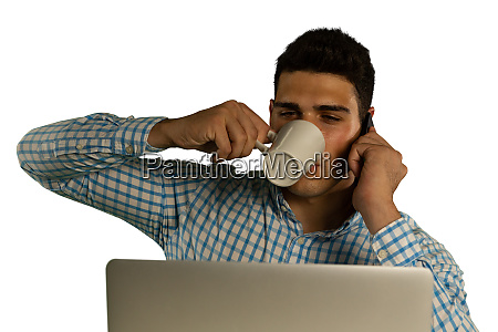 young businessman using a laptop drinking