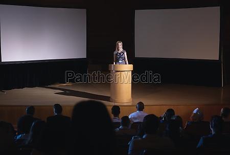 businesswoman standing around podium and giving