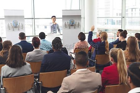 businessman raising hand in a business