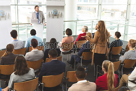 businesswoman interacting with male speaker in