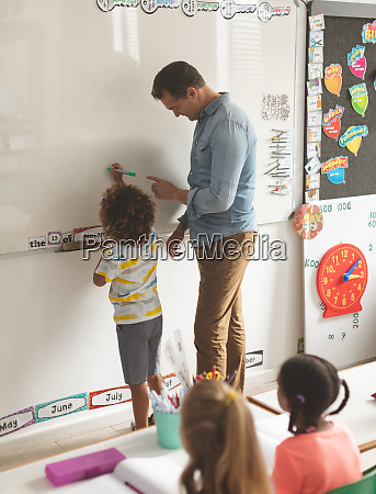 teacher explaining something to schoolchild on