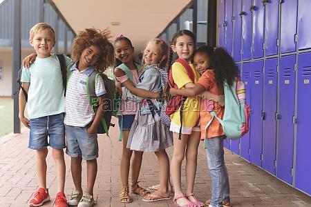 happy school kids standing in corridor