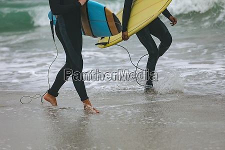 male friends walking on beach while
