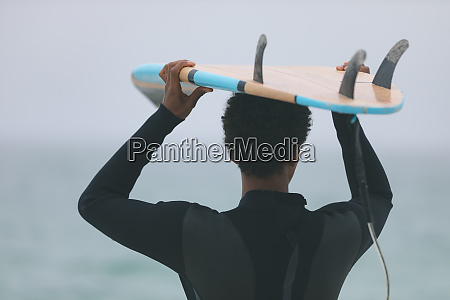 male surfer carrying surfboard on her