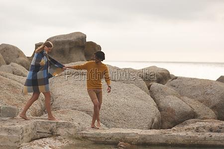 caucasian couple walking on rock near