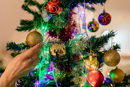 millennial woman decorating christmas tree at
