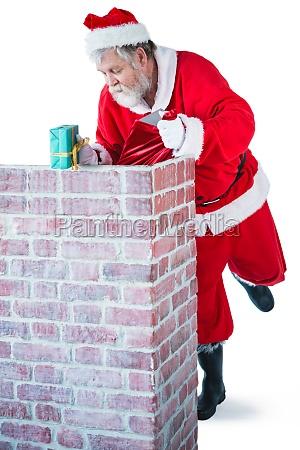 santa claus placing gift box into