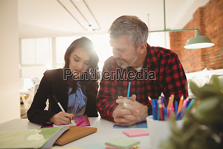 business executives writing on sticky notes