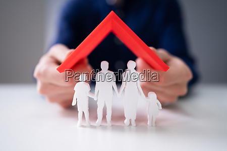 businessman protecting family figures with red