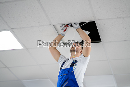 electrician on stepladder installs lighting to