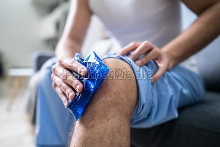 man applying ice gel pack on