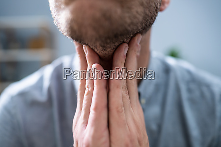 man suffering from sore throat