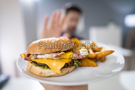 man refusing burger offered by person