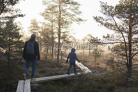 father and son walking on planks