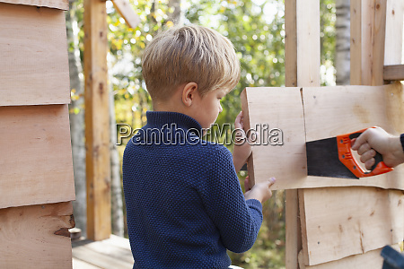 boy learning to build treehouse with