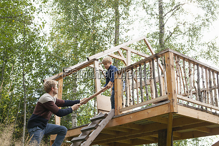 father and son building treehouse together