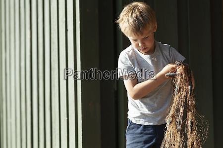 boy holding up tangled fishing net
