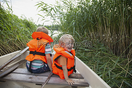 brothers playing on boat moored in