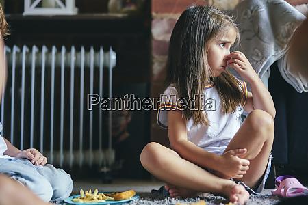 girl sitting on rug beside radiator