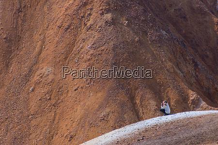hiker taking photograph on peak brennisteinsalda