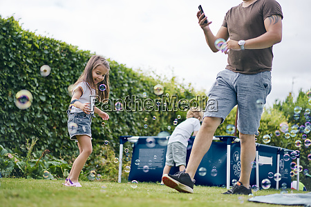 father walking past children playing in