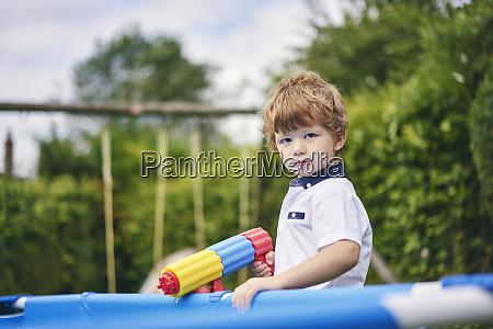 boy holding water gun by pool