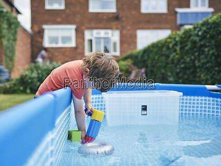 boy filling up water gun from