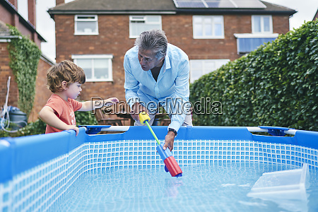 grandfather helping boy fill up water